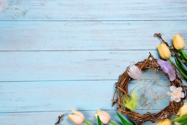 Osternest und -tulpen auf einem hölzernen blauen hintergrund
