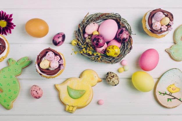 Osternestkleine kuchen, gemalte eier und ingwerbrote auf hellem hölzernem hintergrund