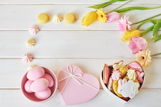 Osterplätzchen in der schachtel mit macarons und blumen