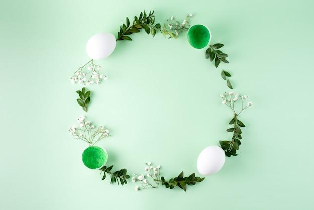 Osterrahmen aus eiern, blumen und grünen zweigen auf grünem hintergrund, draufsicht, flache lage, nahaufnahme.