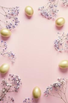 Osterrahmen der purpurroten blumen des goldenen eies auf pastellrosa. draufsicht mit kopierraum.