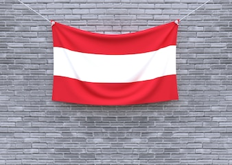 Österreich-Flagge, die an der Backsteinmauer hängt