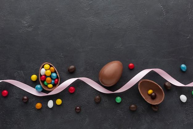 Osterschokoladenei mit bunten süßigkeiten und band