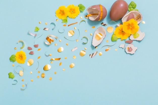 Osterschokoladenei mit goldenen konfetti und frühlingsblumen auf blauem hintergrund