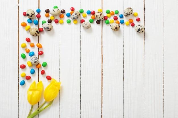 Osterschokoladeneier, bonbons und tulpen auf weißer holzoberfläche