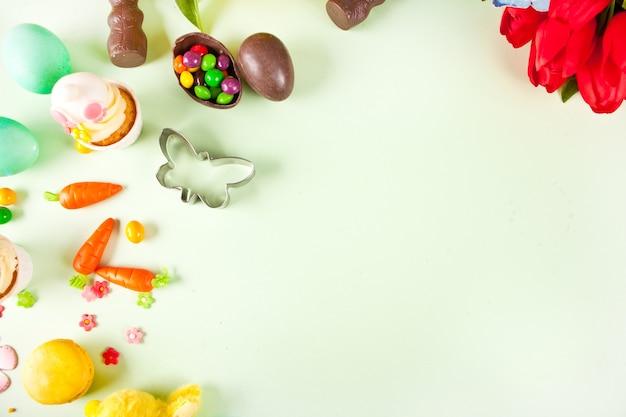 Osterset mit bunten eiern, karotten, süßigkeiten, cupcake. draufsicht. speicherplatz kopieren.