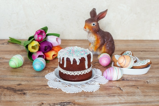 Osterstillleben mit kuchen, hausgemachten keksen, dekorativer kaninchenfigur und ostereiern auf einem holztisch. das konzept, den christlichen osterfeiertag zu feiern.