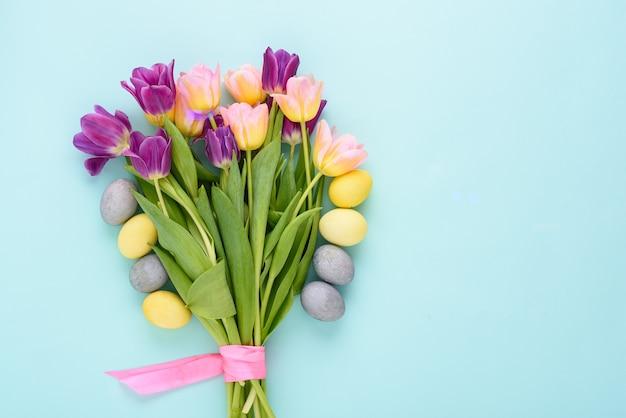 Osterstrauß von lila und rosa tulpen mit pastellgelben und blauen ostereiern auf blauem hintergrund mit kopienraum