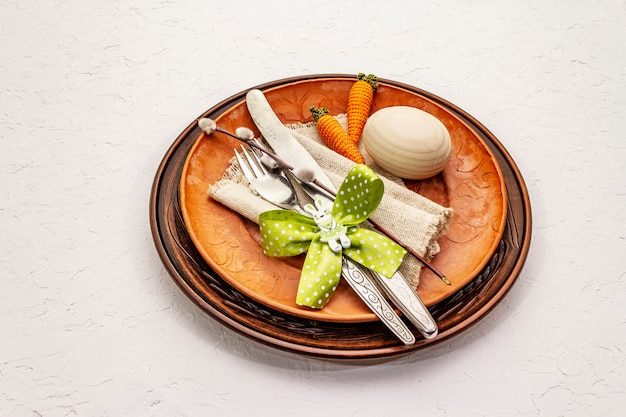 Ostertabelleneinstellung auf strukturiertem weißem kitthintergrund. frühlingsferienkartenschablone. besteck, vintage serviette, ei, karotte, hase