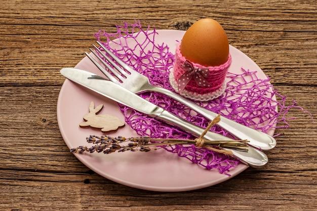 Ostertabelleneinstellung auf weinleseholzbretterhintergrund. frühlingsferienkartenschablone. besteck, ei, lavendel, hase, strickständer