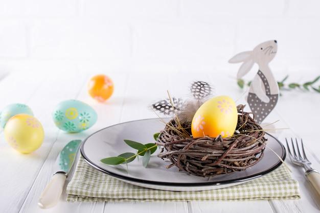 Ostertabelleneinstellung mit weißem teller, gelbem dekorativem hühnerei der textilen serviette im nest, mimosenblumen, federn und frühlings-osterndekoration auf weißem tisch