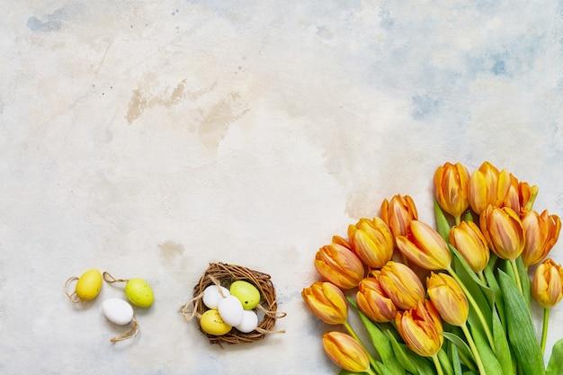 Ostertisch. dekorative ostereier im nest und in den frühlingstulpen auf buntem tisch. kopieren