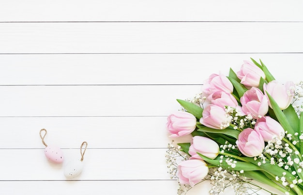 Ostertisch. dekorative ostereier und rosa tulpen auf weißem tisch. speicherplatz kopieren, draufsicht.