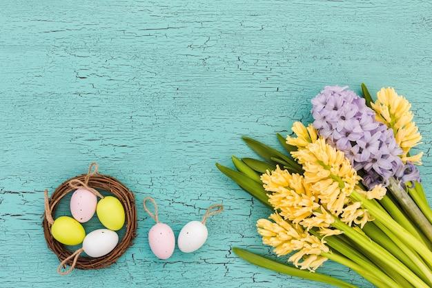 Ostertisch mit blumen und dekorativen eiern. draufsicht, kopierraum