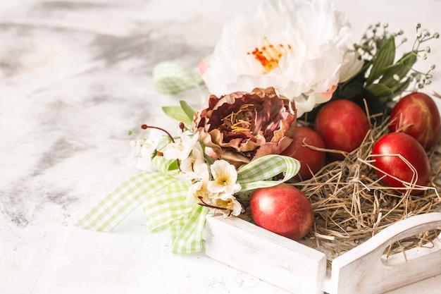 Ostertisch mit einem korb und roten eiern mit blumen