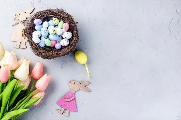 Ostertisch mit farbigen dekorativen eiern im nest und tulpen