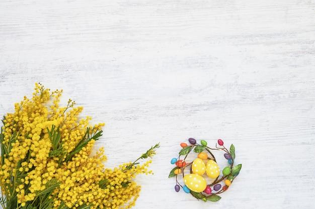 Ostertisch. osterdekoration und mimosenstrauß auf weißem tisch. draufsicht, kopierraum.