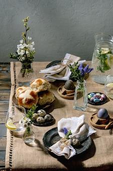 Ostertischgedeck mit farbigen und schokoladeneiern, heißen kreuzbrötchen, blumenstraußblumen, leerem keramikteller mit serviette, glas limonadengetränk auf holztisch mit textiler tischdecke
