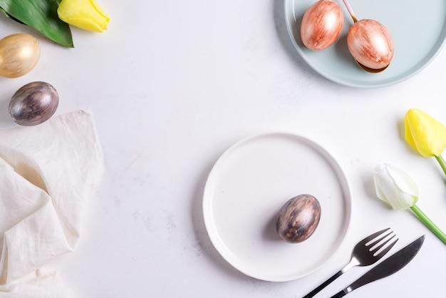 Ostertischgedeck mit frühlingstulpen. eleganter leerer teller, besteck, serviette und goldene eier auf stein