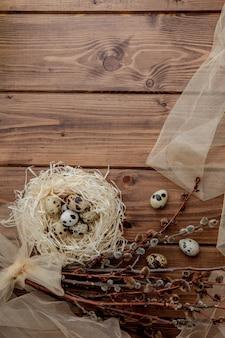 Osterwachteleier im nest und im weidenzweig auf einem hölzernen hintergrund, kopieren raum