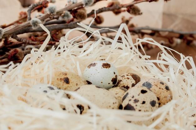 Osterwachteleier im nest und im weidenzweig auf einem hölzernen hintergrund