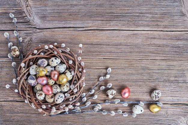 Osterweidenkranz und bunte wachtel-ostereier auf altem hölzernem hintergrund. draufsicht, kopierraum