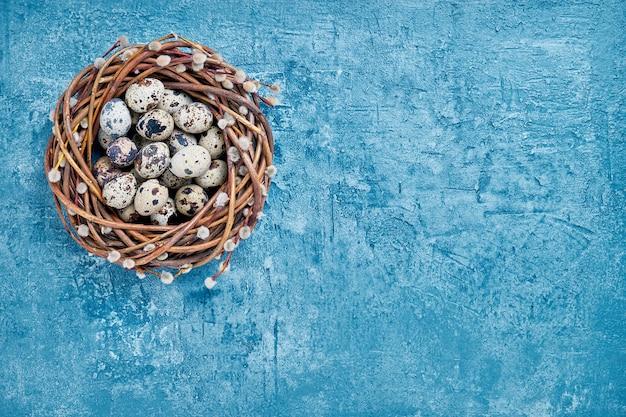 Osterweidenkranz und osterwachteleier auf blauem hintergrund