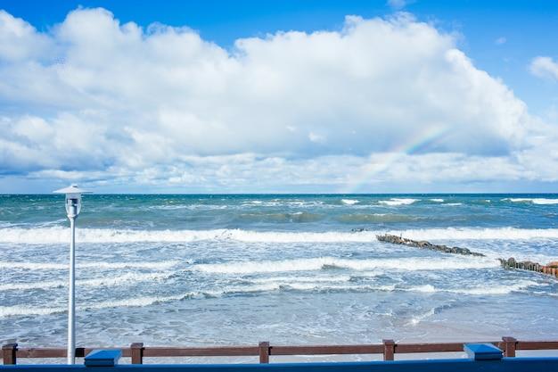 Ostseestrandlandschaft mit blauem meer, schönen weißen wolken und einem regenbogen am sonnigen herbsttag.