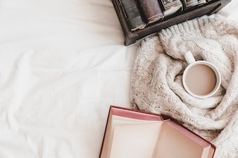 Otebook und Kasten mit Büchern nähern sich heißem Getränk im Plaid