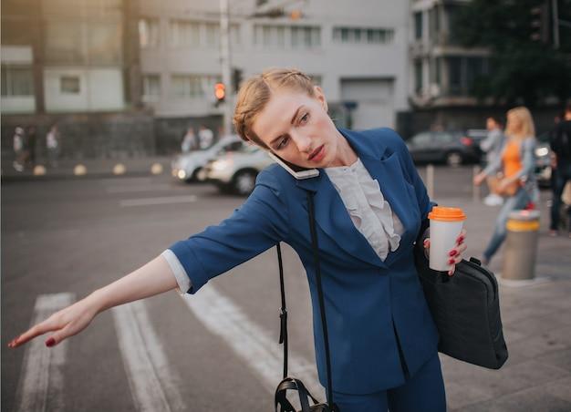 Oung stilvolle geschäftsfrau mit kaffeetasse, die ein taxi fängt. frau, die mehrere aufgaben macht. multitasking-geschäftsfrau.