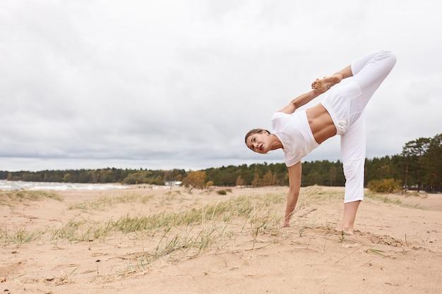 Outdoor-bild in voller länge von einer konzentrierten kaukasischen frau, die ein weißes outfit trägt, yoga im freien macht, mit einem fuß und einer hand auf sand steht, balance, konzentration und koordination trainiert