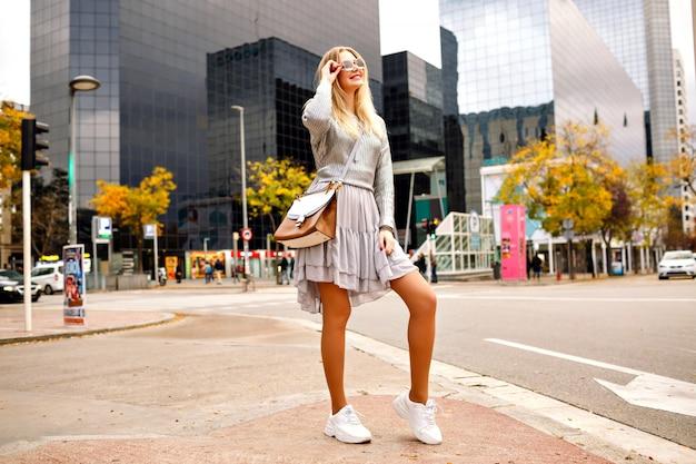 Outdoor-bild in voller länge von stilvoller frau, die durch ihr smartphone spricht, das nahe modernem gebäude aufwirft, lässiger stilvoller hipster-look, frühlingssherbstzeit der zwischensaison.