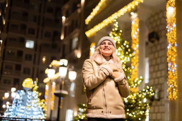 Outdoor-foto des jungen schönen glücklichen lächelnden mädchens, das wunderkerzen hält und in der straße aufwirft. festlicher weihnachtsmarkt im hintergrund. modell mit stilvollem wintermantel, strickmütze, schal.