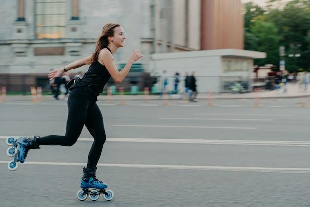 Outdoor-foto einer aktiven dunkelhaarigen frau in guter körperlicher verfassung genießt extreme sportfahrten auf rollen entlang der straße auf der belebten straße, entspannt sich am wochenende im freien. gesundes lebensstilkonzept