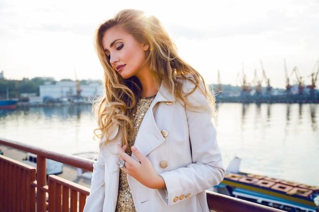 Outdoor-herbstmodeporträt der sexy eleganten dame, die ordentlich seehafen aufwirft, der träumt und denkt, weißen kaschmir weißen mantel trägt, hat gekräuselte haare und helles make-up. abendsonne, sanfte farben.
