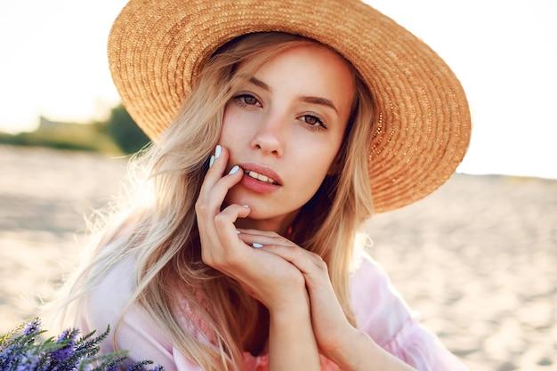 Outdoor-lebensstilporträt der anmutigen weißen frau, die auf sonnigem strand nahe ozean steht. strohhut tragen. naturhintergrund. warme weiche farben.