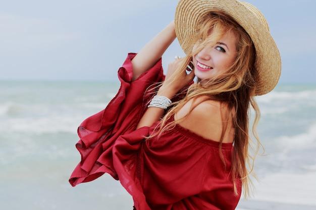 Outdoor-lebensstilporträt der hübschen weißen ingwerfrau im stilvollen kleid, das auf dem strand nahe ozean aufwirft. blu himmel. windiges wetter.
