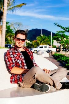 Outdoor-lebensstilporträt des jungen hipster-mannes, der weinlesesonnenbrille und kariertes hemd trägt