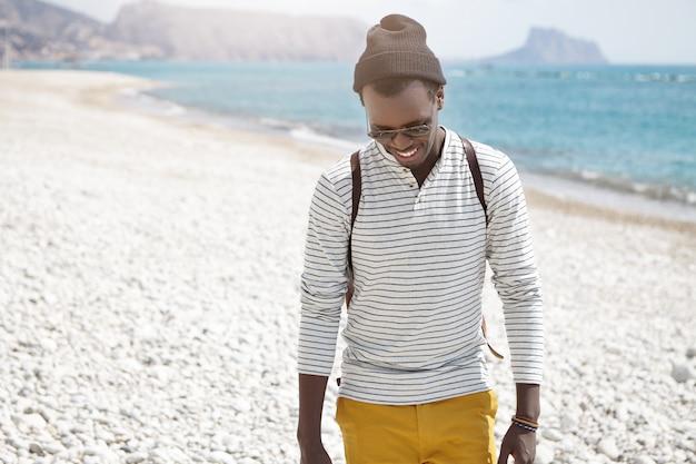 Outdoor-lebensstilporträt des stilvollen jungen mannes mit rucksack und sonnenbrille, die auf sonnigem europäischem strand gehen, verwirrtes lächeln tragen, auf kiesel herabblickend
