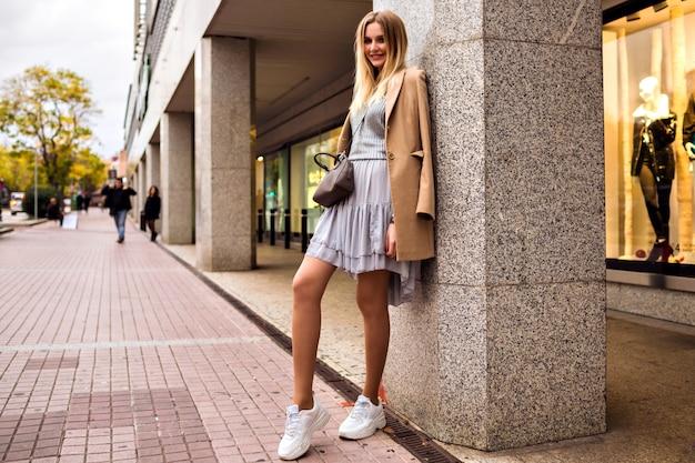 Outdoor-lifestyle-modeporträt einer hübschen, eleganten, glamourösen, blonden frau mit langen beinen, die trendige turnschuhe, einen pullover und einen mantel trägt und in europa posiert und alleine reist.