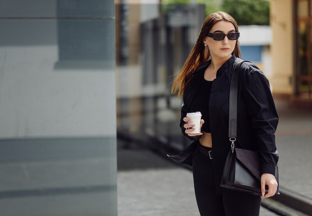 Outdoor-lifestyle-porträt des atemberaubenden brünetten mädchens. kaffee trinken und auf der stadtstraße spazieren gehen.