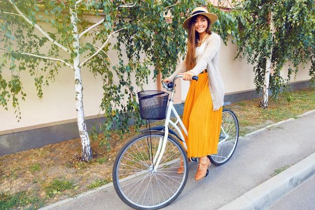 Outdoor-mode-lifestyle-porträt des schönen jungen brünetten mädchens, das ihr retro-fahrrad auf der straße mit birken reitet. tragen eines eleganten, stilvollen kleiderhutes und einer warmen strickjacke. herbststimmung.