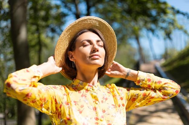 Outdoor-mode nahes porträt der frau im gelben sommerkleid und im hut im park, die heiße sommertage genießt