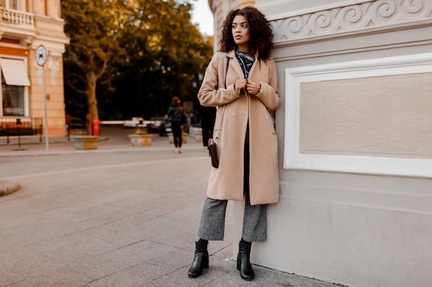 Outdoor-mode-porträt der glamourösen sinnlichen jungen stilvollen schwarzen dame, die trendiges herbstoutfit, grauen samtpullover und beigen wollmantel trägt.