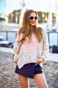 Outdoor-mode-porträt der hübschen blonden frau, die allein am schönen sonnigen herbsttag, gemütlicher schwader-minirock, abendsonnenlicht geht.