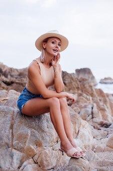 Outdoor-mode-porträt der jungen europäischen frau in den blauen jeansshorts des beigen körperbodysuit und des klassischen stilvollen hutes auf warmem sonnenuntergangslicht des tropischen felsigen strandes