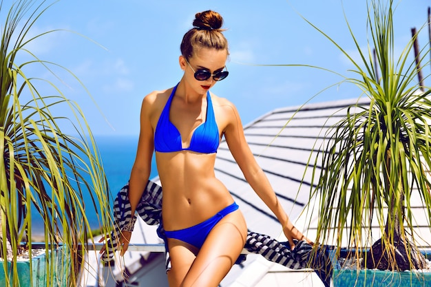 Outdoor-mode-porträt der jungen sexy model-frau mit perfektem, schlank gebräuntem körper, genießen sie ihre sommerferien in einer luxusvilla, einen atemberaubenden blick auf den inselozean, tragen sie einen bikini und eine sonnenbrille.