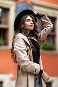 Outdoor-mode-porträt der sinnlichen jungen stilvollen dame des glamours, die trendiges herbstoutfit und schwarzen hut auf der straße trägt
