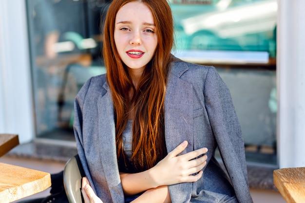 Outdoor-mode-porträt der stilvollen ingwerfrau, die im terrassencafé, am sonnigen tag aufwirft, trägt freundjacke, helle frische farben.