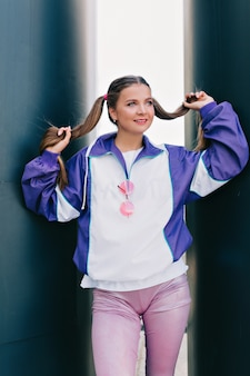 Outdoor-mode-porträt des jungen charmanten weiblichen modells, das helle jacke und rosa hosen mit gesammeltem haar trägt, das mit leichtem lächeln aufwirft